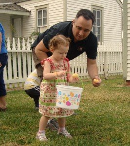 Madeline Schimmer gets a little help from dad in the egg hunt